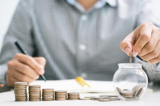 Feche a calculadora de contabilidade do homem de negócios com a economia de moedas empilhadas em linha com a mão colocando as moedas no vidro do jarro