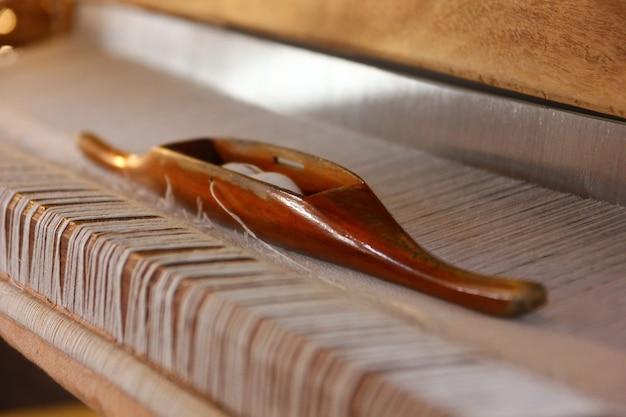 Feche a canela de madeira e o fio de algodão branco na máquina de tecelagem local do tear de madeira.