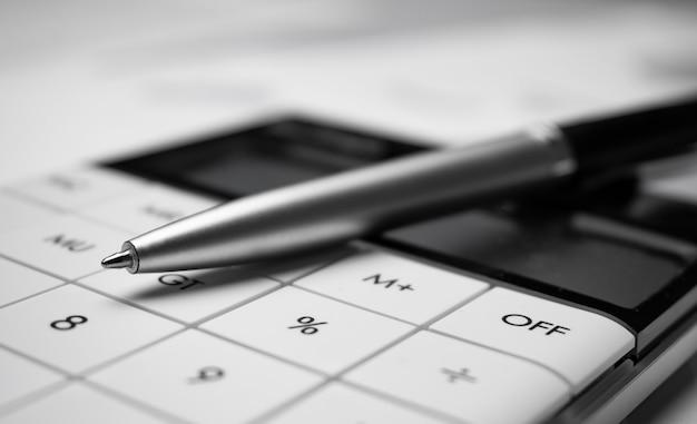 Feche a caneta e a calculadora sobre os gráficos em preto e branco