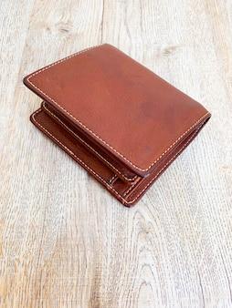 Feche a carteira luxuosa de couro marrom colocada no fundo da mesa de madeira