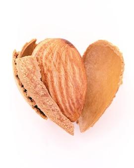 Feche a casca da noz de amêndoas rachada em forma de coração isolada no fundo branco. amo o conceito de alimentação saudável.