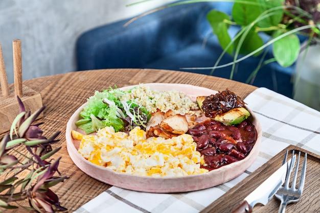 Feche a comida. café da manhã inglês tradicional da culinária moderna com espaço da cópia. comida de restaurante. bulgur, salada verde, feijão, abacate, cebola caramelizada, omelete, frango no prato. copie o espaço