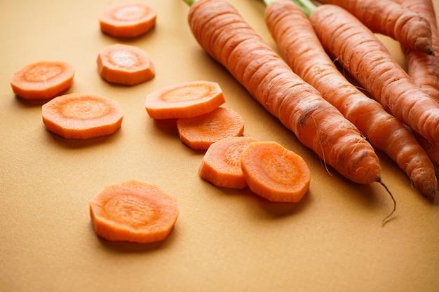 Feche a composição com cenouras frescas maduras e fatias