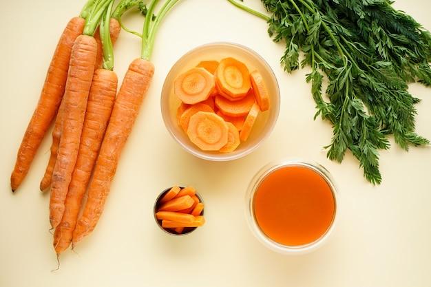 Feche a composição com cenouras frescas maduras, suco e fatias