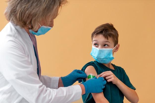 Feche a criança e o médico usando máscaras