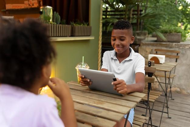 Feche a criança sentada à mesa com o tablet
