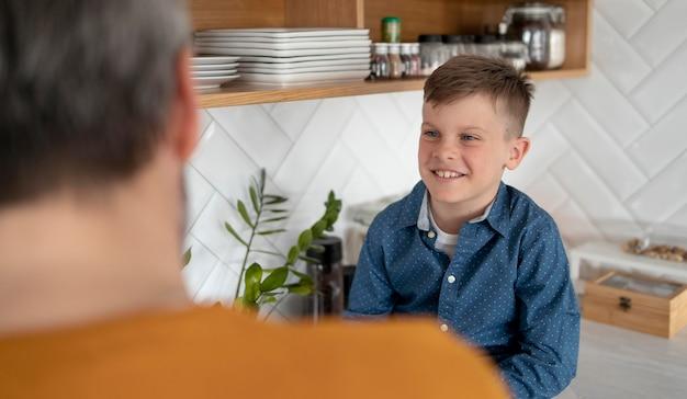 Feche a criança sorridente e os pais dentro de casa