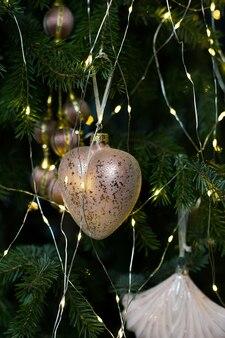 Feche a decoração da árvore de natal e ano novo com um brinquedo de coração dourado brilhante com galhos de pinheiro e luzes de guirlanda