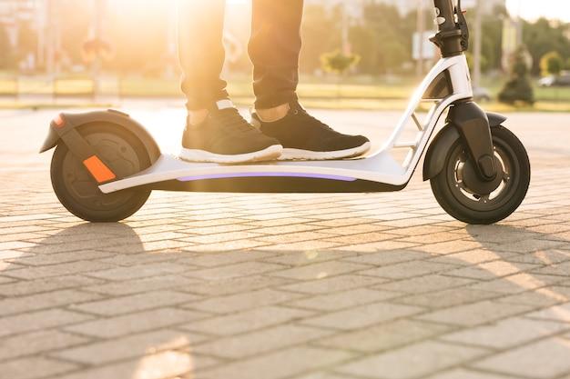 Feche a entrega de comida de correio de homem de pés anda na rua em scooter elétrico entregar cliente de pedido on-line ao pôr do sol. tiro nas pernas, jovem de tênis preto andando de scooter elétrico móvel