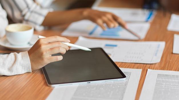 Feche a equipe de negócios usando um tablet com caneta stylus e olhando os documentos financeiros