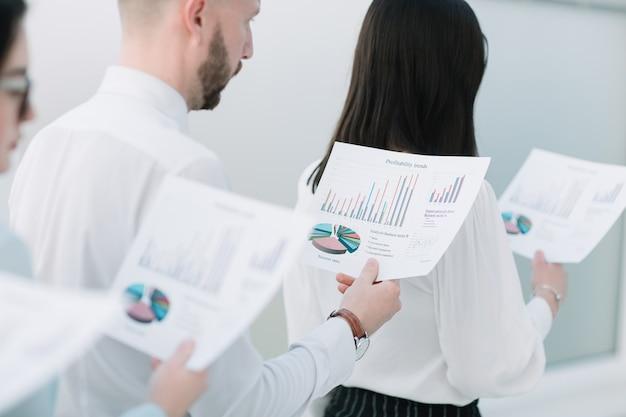 Feche a equipe de up.business com dados financeiros em pé na fila. conceito de negócios