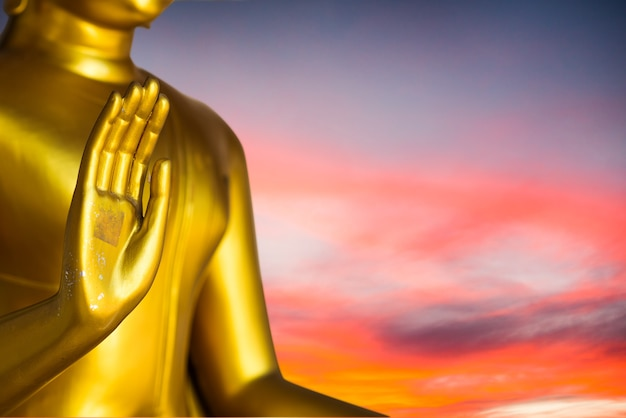 Feche a estátua de buda com cru de latão. mão da estátua de buda com a mão da folha aberta para a frente no pôr do sol backgroud. acredite, cultura, tradicional. conceito budista. conceito de calma. conceito de meditação.