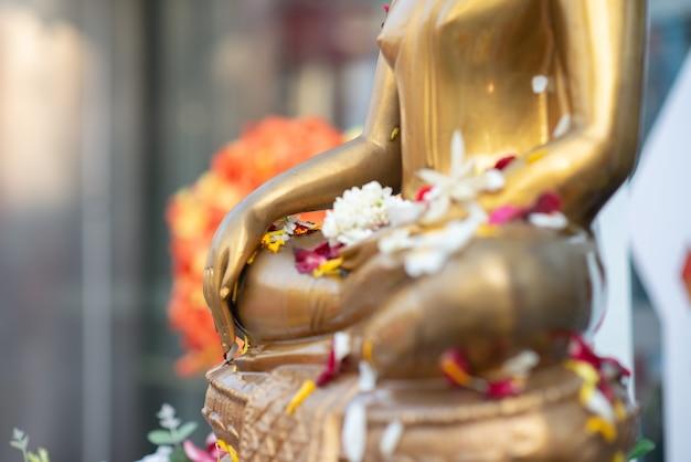 Feche a estátua de buda com cru de latão. mão da estátua de buda com folha no colo de buda.