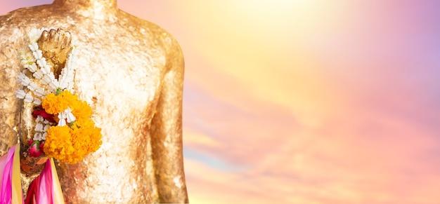 Feche a estátua de buda com cru de latão. mão da estátua de buda com. guirlanda de calêndula amarela no fundo do sol do céu. acredite, cultura, tradicional. budista e mérito. conceito de calma e meditação.