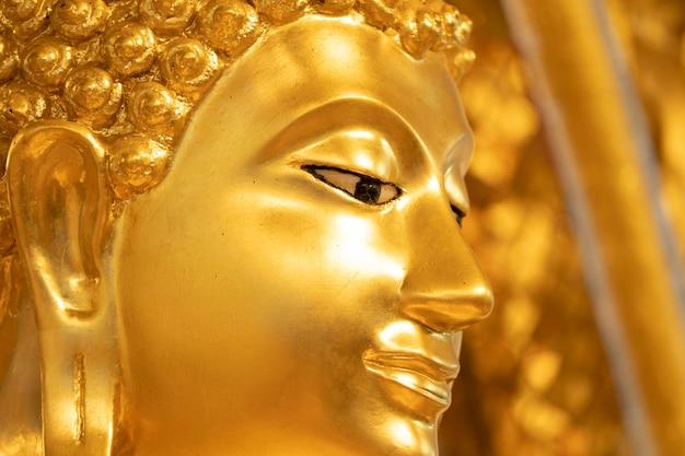 Feche a estátua de buda de ouro face para segundo plano.