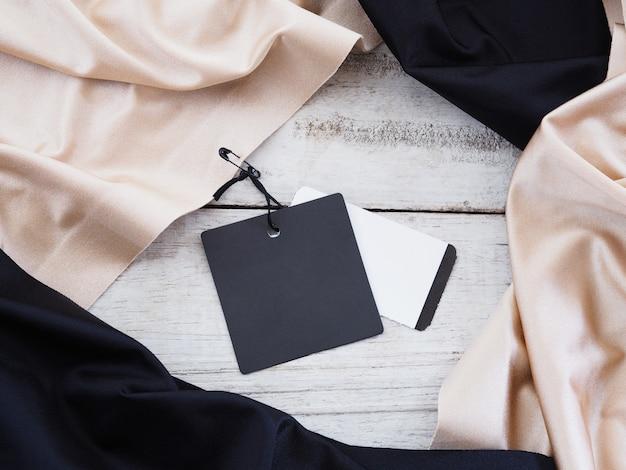 Feche a etiqueta de venda de papel preto pendurada em um pano de seda sobre o fundo branco de madeira vintage.