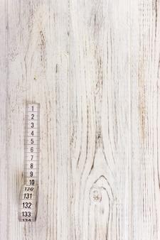 Feche a fita métrica de alfaiate no fundo da mesa de madeira. departamento de campo raso da fita métrica branca.
