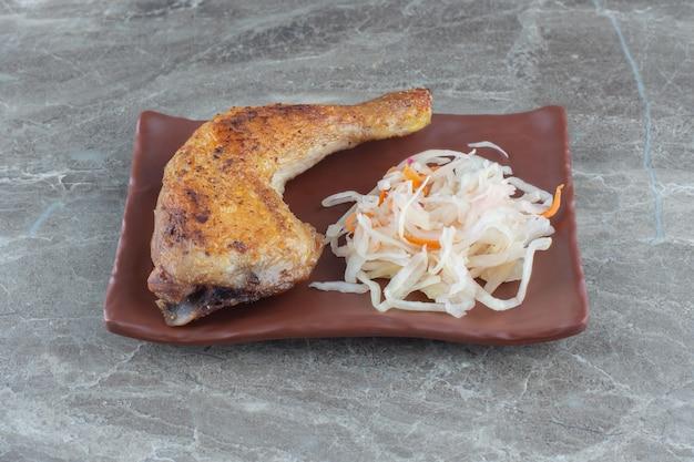 Feche a foto da coxa de frango grelhado com chucrute no prato de cerâmica marrom.