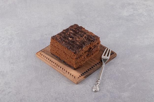 Feche a foto da fatia de bolo de chocolate na placa de madeira sobre um fundo cinza.