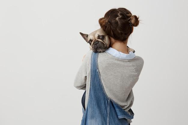 Feche a foto da garota com cabelo em pães duplos em pé traseiros segurando seu cachorro nas mãos. adolescente feminino vestindo macacão jeans expressar amor ao seu bulldog francês. sentimentos, atitude