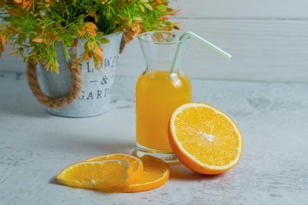 Feche a foto da laranja em fatias com um copo de suco de laranja.
