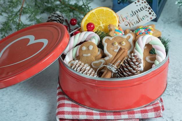 Feche a foto da louça vermelha cheia de biscoitos caseiros.