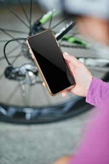 Feche a foto da mão de uma ciclista segurando o smartphone enquanto verifica os mecanismos da bicicleta