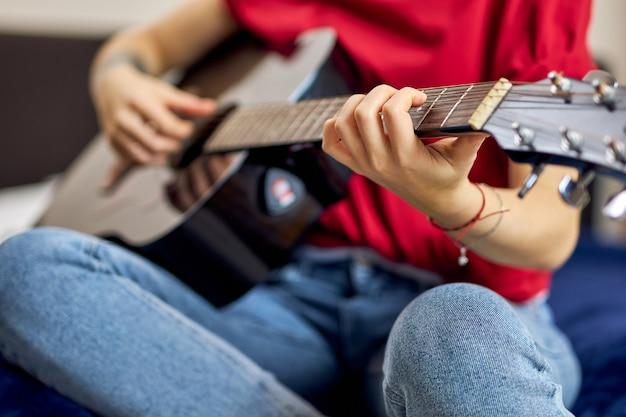 Feche a foto da mão de uma jovem com roupas casuais, tocando violão