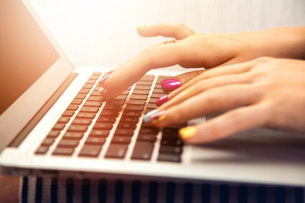 Feche a foto da mão de uma mulher digitando no trabalhador laptop