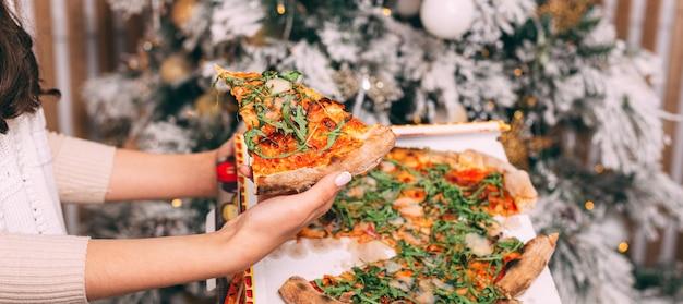 Feche a foto da mão de uma mulher segurando uma fatia de pizza fresca sobre o fundo da árvore de natal