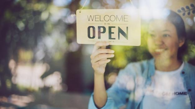 Feche a foto da mão de uma mulher, virando a placa de sinal aberto na porta de vidro no café e no restaurante.