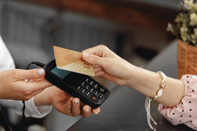 Feche a foto da mão do cliente pagando com cartão de crédito sem contato