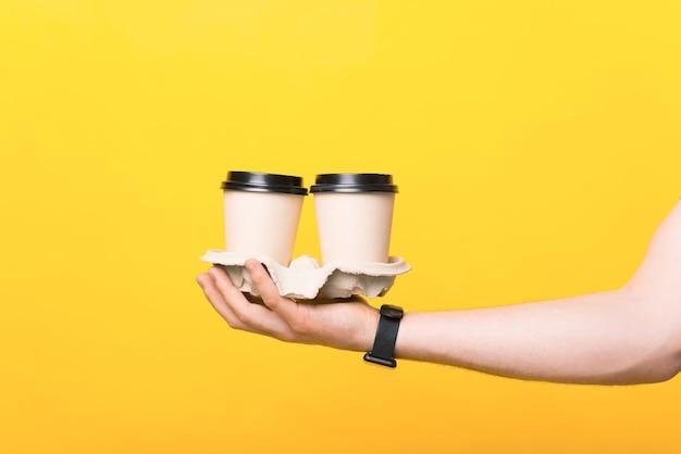 Feche a foto da mão do homem segurando dois copos de papel com café para viagem