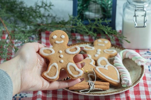 Feche a foto da mão feminina pegando o biscoito do prato.
