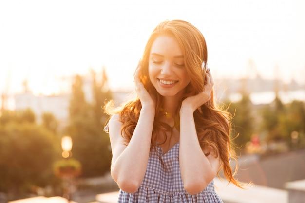 Feche a foto da mulher atraente gengibre no vestido ouvindo música por do sol e olhando para baixo