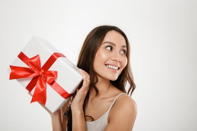 Feche a foto da mulher caucasiana encantada, olhando de lado enquanto mostra a caixa de presente com fita vermelha na câmera, isolada sobre o branco