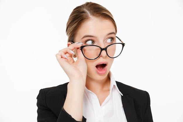 Feche a foto da mulher de negócios loira chocada em óculos, olhando para longe sobre o branco