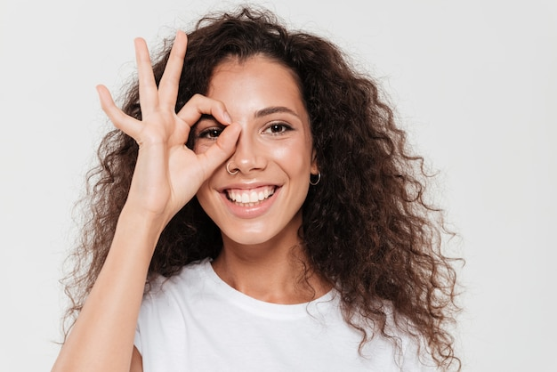 Feche a foto da mulher encaracolada sorridente, segurando a mão no rosto e mostrando sinal okey