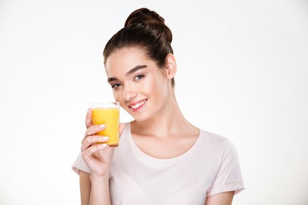 Feche a foto da mulher linda feliz bebendo suco de laranja doce de vidro transparente com sorriso
