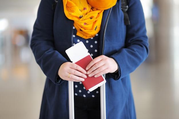 Feche a foto da mulher segurando o passaporte e o cartão de embarque no aeroporto