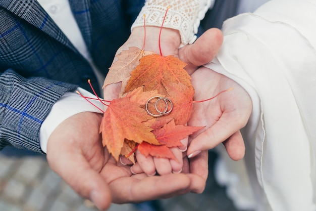 Feche a foto da noiva e do noivo com as mãos segurando os anéis de casamento