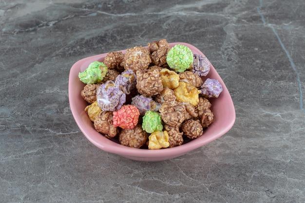 Feche a foto da pilha de doces coloridos caseiros em uma tigela rosa.