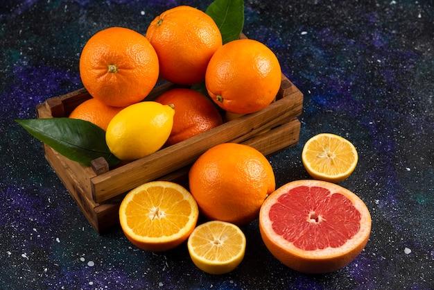 Feche a foto da pilha de frutas cítricas em um laço de madeira.