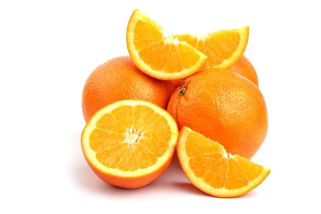 Feche a foto da pilha de laranjas inteiras ou fatiadas, isoladas na superfície branca.