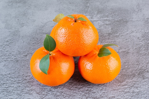 Feche a foto da pilha de tangerina orgânica em cinza.