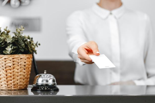 Feche a foto da recepcionista do hotel dando a chave da porta