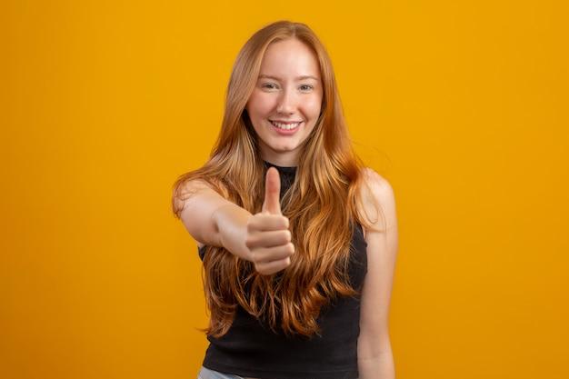Feche a foto da senhora muito sexy, levantando o polegar, expressando o acordo usar camisa quadriculada camisa casual isolada cor amarela parede. ok.