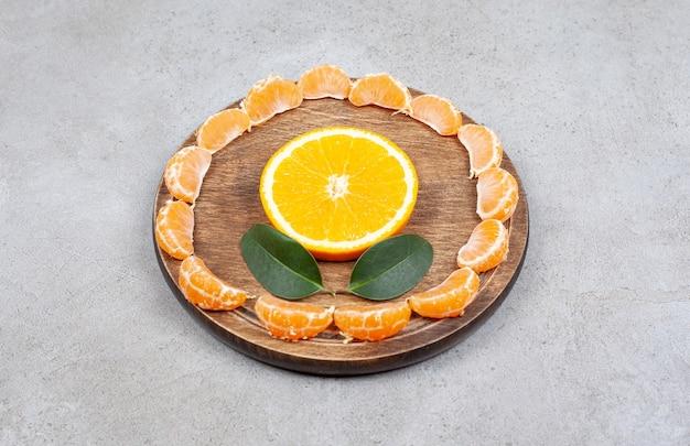 Feche a foto das fatias de tangerina em torno da fatia de laranja na placa de madeira.