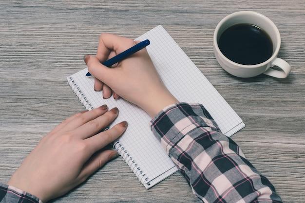 Feche a foto das mãos da garota escrevendo a composição.