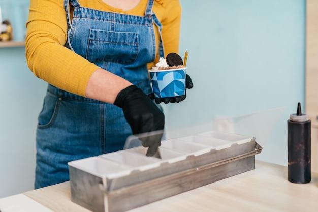 Feche a foto das mãos da trabalhadora trabalhando em uma sorveteria artesanal.